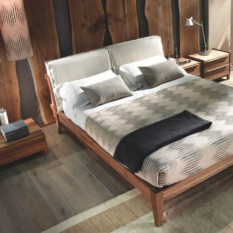 Bed in solid walnut or oak with pillows in fabric